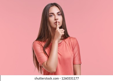 Beautiful surprised young female demonstrates silence gesture, keeps forefinger on lips, dressed casually, isolated on pink studio background. Body language concept