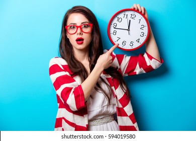 beautiful surprised young woman with clock standing in front of wonderful blue background
