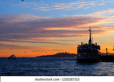 Beautiful suset in Bosphorus Channel with ferryboat, Istanbul, Turkey. Ship at Besiktas. Seaguls fly in Istanbul at suset.