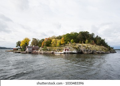 The beautiful swedish archipelago at the stockholm coast. An little island with swedish houses and autumn trees.