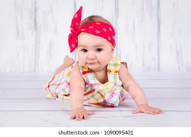 Beautiful sweet baby girl crawling on the floor, wearing head scarf and looking towards camera