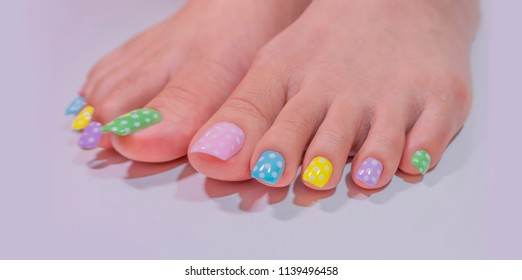 beautiful sweet colorful pink green yellow purple blue gel polish painting cute white polka dot on fashionista woman toenails isolated on white background