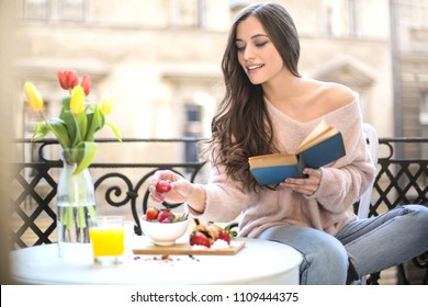 Beautiful sweet girl having breakfast in the balcony while reading a book