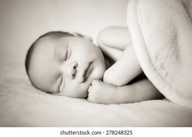 beautiful sweet newborn baby sleeping on a blanket. Black and white photo