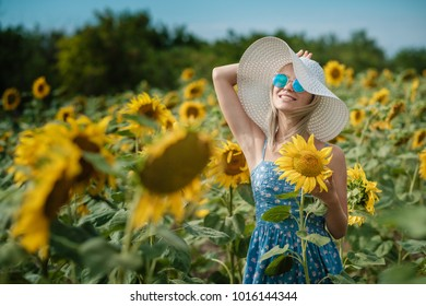 beautiful sweet sexy girl in a blue dress walking on a field of sunflowers , smiling a beautiful smile and photo sun shines bright and juicy