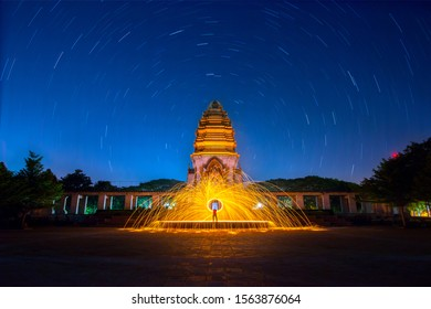 Beautiful Swing fire dancing show at night with star trail background.Swirl Steel Wool light Photography at Stone castle at Koh Klang nam public park in Sisaket Thailand. - Shutterstock ID 1563876064