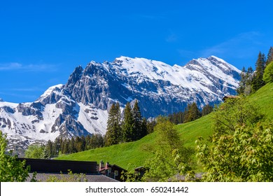 Beautiful Swiss mountain valley landscape with a house roof.