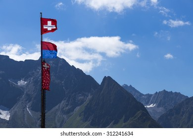 beautiful switzerland flag with mountain background on summer period on a pole in mountains.