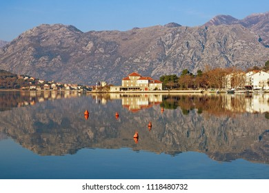 Beautiful symmetrical landscape where mountains and coast are reflected in water. Montenegro, Bay of Kotor, Dobrota town
