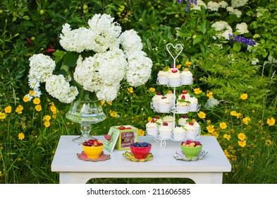 Beautiful table with mascarpone cupcakes, fresh berries and flowers, set in a summer garden
