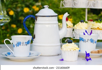 Beautiful table with mascarpone cupcakes, vintage teapot and cups and flowers, set in a summer garden