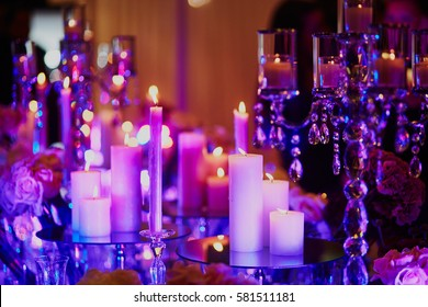 Beautiful table set with candles for a festive event, party or wedding reception, in purple light