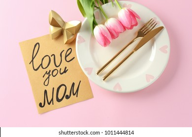 Beautiful table setting with card for Mother's Day Brunch on color background