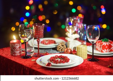 Beautiful table setting for Christmas party or New Year celebration at home. Cozy room with a fireplace and Christmas tree in a background. Xmas time with family and friends.
