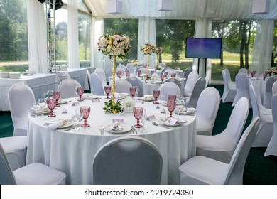 Beautiful table setting with crockery and flower arrangement in a vase on a high stem for a party, wedding reception or other festive event. Glassware and cutlery for catered event dinner.