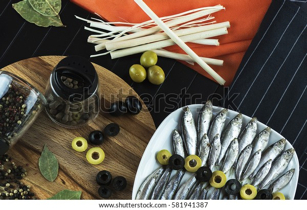 Beautiful table setting on the table from a small fish of the sprat, seasonings and olives