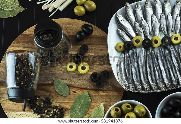 Beautiful table setting on the table from a small fish of the sprat, condiments, olives and decor. The view from the top
