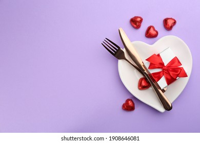Beautiful table setting on violet background, flat lay with space for text. Valentine's Day dinner
