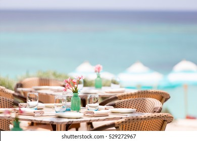 beautiful table setting in pastel tones in outdoor cafe at the beach or resort