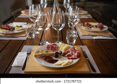 Beautiful table setting in a restaurant with glasses and snacks. Italian gourmet restaurant. Cozy interior in the cafe. Wine glasses