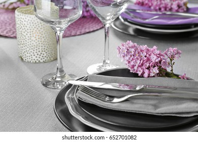 Beautiful table setting with silver cutlery and lilac as floral decor