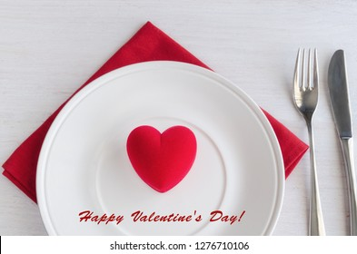 Beautiful table setting in white red tone for celebrate St Valentines Day. Plate, cutlery, line napkin and red heart shape gift box. Love romantic dinner concept.