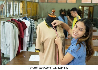 beautiful tailor women smiling when measure the mannequin chest width with tape measure at the clothing garment room