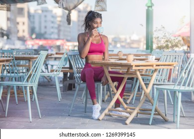 Beautiful tall athletic African American Woman wearing a bright pink workout outfit sits in an outdoor cafe drinking   coffee or tea in deep though  on a bright sunny day
