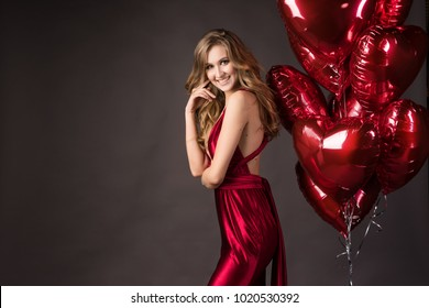 Beautiful tall slender blond girl wearing a deep neckline red satin dress posing with red balloons in the shape of a heart. Valentine's Day, holidays, party. Advertising, fashion and commercial Design