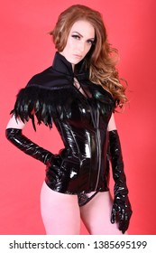 Beautiful, tall, slim, busty Redhead dressed in a Fetish PVC outfit, isolated against a red background, sometimes topless