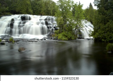 The beautiful tall wide waterfall at Bond Falls Michigan.  A time exposure captures the special appearance. Located in the Upper Peninsula at Haight Township, Michigan along the Ontonagon River.