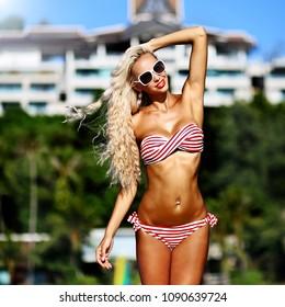 Beautiful tan blonde woman in bikini and sunglasses
