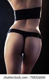 beautiful tan female body in lingerie on black background