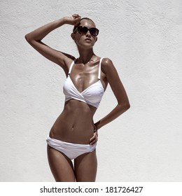 Beautiful tan female model posing in bikini and sunglasses. Against white wall.