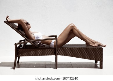 Beautiful tan female model sunbathing in bikini on chaise-longue. Against white wall.