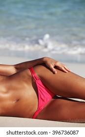 Beautiful tan woman in swimwear laying on beach