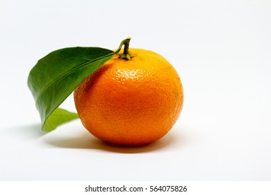 Beautiful tangerine (mandarin) with leaf on a white background. selective focus