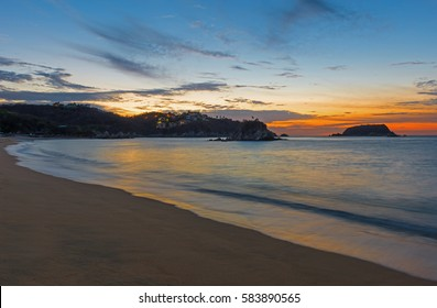 The beautiful Tangolunda Bay at sunrise with a long exposure and beautiful colors. The bay is a part of the Huatulco beach resort in Mexico.