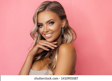 Beautiful tanned blond woman with wavy long hair in diamond accesories posing on pink background