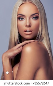 Beautiful tanned blond young woman with long straight hair and soft glamorous make up posing in the studio.