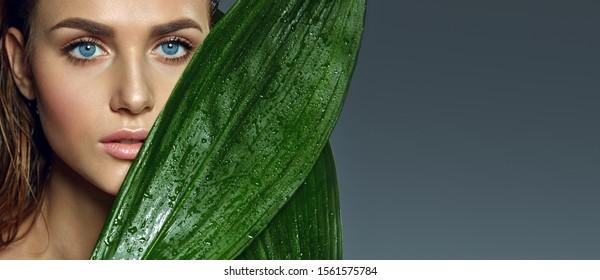 Schönes gegerbtes blauäugiges Mädchen mit natürlichem Make-up und nassem Haar hält feuchte exotische Blätter in der Nähe ihres Gesichts.