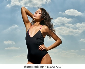 Beautiful, tanned girl in black, fused bikini on blue sky background with clouds. At sea.