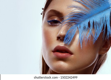 Beautiful tanned girl with creative make-up and blue eyelashes, feather in hand. Beauty face. Photo taken in the studio.
