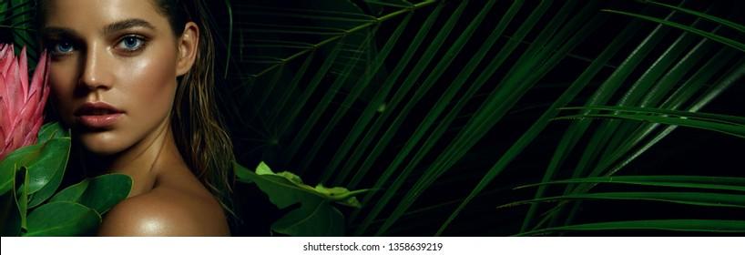 Ein wunderschönes gegerbtes Mädchen mit natürlichen Schminken und nassen Haaren steht im Dschungel zwischen exotischen Pflanzen.Mode, Schönheit, Gesundheit, Ökologie, Make-up, persönliche Pflege, Haare, Natur.
