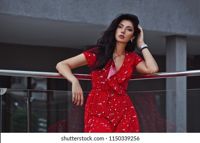 A beautiful tanned girl stands on terrace or veranda. Cute girl in a red dress. Everyday life of a beautiful young lady.