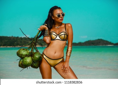 beautiful tanned girl in trendy bathing suit sunglasses stands with a bunch of coconuts in her hands on beach tropical island. Summer vacation, travel around the world, advertising swimwear new season