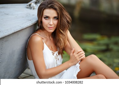 A beautiful tanned girl in a white dress sits by the boat and is sad, in nature in summer