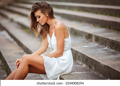 A beautiful tanned girl in a white dress is sitting on the stairs and sad, on nature in summer