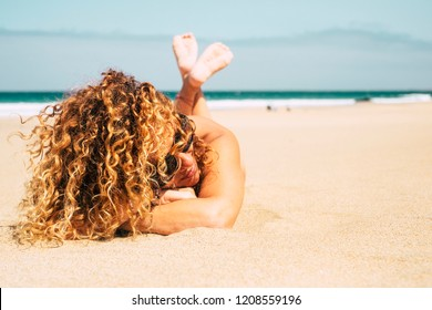 Beautiful tanned lady middle age attractive with curly blonde hair lay down at the beach for a summer sun bath during vacation. relaxed attractive woman in summer time in holiday on the sand