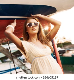 beautiful tanned sexy ginger girl in yellow summer dress and sunglasses stands under blue-and-red boat in sun rays
